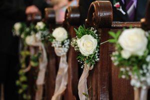 Mit weißen Rosen geschmückte Kirchenbänke (Hochzeit)